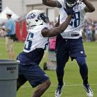 Tennessee Titans running back Chris Johnson (28) tries to put a ball into a waste can as running back Darius Reynaud (25) tries to block him out during a drill at camp in Nashville.