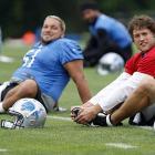 Detroit Lions quarterback Matthew Stafford, right, stretches with center Dominic Raiola in Allen Park, Mich.