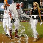 Randall Delgado is doused by teammate Martin Prado as sideline reporter Jody Jackson moves out of the way, following Delgado's three-hitter for his first career shutout in the Diamondbacks 10-0 rout over the Padres.
