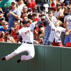 Shane Victorino of the Red Sox leaps over the right field wall in an attempt for a foul ball in an Aug. 4 game against the Diamondbacks in Boston.