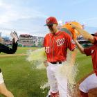 Stephen Strasburg is doused by teammates Tyler Clippard and Craig Stammen (right) as reporter Julie Alexandria darts out of the way following Strasburg's first complete game in the Nationals' 6-0 win over the Phillies.