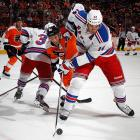 New York Rangers forward Tyler Pratt (14) navigates the wall while shielding the puck from Philadelphia Flyers forward Vincent Lacavalier