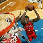 Amir Johnson of the Toronto Raptors finishes through contact against the Minnesota Timberwolves in a preseason game.