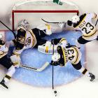 Boston Bruins goaltender Tuukka Rask gets a hand from teammates defending the net against the Florida Panthers.
