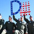 """Air Force fans hold up an American flag-themed """"Defense"""" sign as the Falcons make a big fourth-down stop against Army in November."""