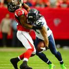 Seahawks running back Marshawn Lynch stiff arms Falcons defensive back William Moore. Seattle won easily, 33-10, and moved to an NFC-best 9-1.