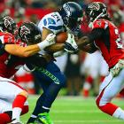 "Seahawks running back Marshawn Lynch lives up to his ""Beast Mode"" nickname as he runs through three Atlanta Falcon defenders. Lynch finished with 145 yards and a score on 24 carries."
