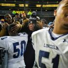 Abraham Lincoln players Kadeki Kelly (50) and Douglas Powell (51) celebrate with fans after winning the title game.