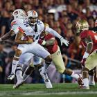 Quarterback Nick Marshall attempts to elude several 'Noles defenders.