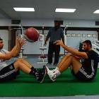 NMSU strength and conditioning coach Trei Steward (background) has to devise alternate workout routines to accommodate the Bhullar brothers since they don't fit onto traditional weight benches or strength training machines.