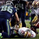 Marshawn Lynch (24) was credited with a fumble recovery on this play as he and others dove on top of the injured NaVorro Bowman and wrestled for the ball.