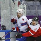 Shattered dreams: Austrian forward Andreas Nodl checked Norway defenseman Jonas Holos into the glass during their preliminary round shinny game in Sochi. Neither team managed to medal.