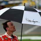 Kevin Harvick takes cover under an umbrella during the rain delay.