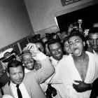 """A sweet moment: Still celebrating and proclaiming himself the """"greatest,"""" Clay returned to his dressing room escorted by the great Sugar Ray Robinson (in tie), and trailed by his longtime friend and handler Drew (Bundini) Brown (over Ali's right shoulder)."""