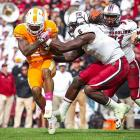 Clowney tries to pry the ball from Tennessee running back Rajion Neal.