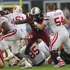 Clowney knocks the helmet off Wisconsin Badgers offensive linesman Kyle Costigan as he tries to get to Badgers running back Melvin Gordon during the Capital One Bowl.