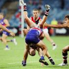 Eli Templeton of the Australian Football League's St. Kilda Saints tumbles over Koby Stevens of the Western Bulldogs during a round two AFL NAB Challenge Cup match. The Bulldogs topped the Saints.