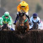 Jockey Ian Popham and horse Bally Legend clear the final hurdle to win the BetBright Chase in Sunbury, England.