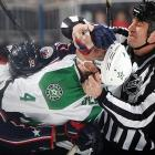 Linesman Derek Amell attempts to mediate a scrum between R.J. Umberger of the Columbus Blue Jackets (No. 18) and Brenden Dillon of the Dallas Stars (No. 4). Umberger scored a goal in the first period, helping Columbus to a 4-2 win.