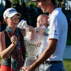 The rookie duffer and his spouse Amanda delight at the valuable prizes awarded after his triumph in the Puerto Rico Open at toney Trump International Golf Club in Rio Grande. Among his winnings were a handsome glass punch bowl and a tiny tot.