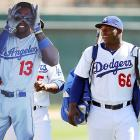 Dodgers outfielder Yasiel Puig (right), third sacker Juan Uribe (obscured), and a life-sized cutout of shortstop Hanley Ramirez make their way to a Cactus League game against the Oakland at Camelback Ranch in Glendale, AZ. In the ensuing action, Puig took an 0-for-3 collar, Uribe went for 2-for-3 with a solo dinger, and the Ramirez cutout chipped in with two hits, but its limited range in the field proved costly as the A's rallied for five runs in the eighth inning en route to an 8-8 tie.