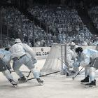Washington center Nicklas Backstrom (19), who had two assists in the game, goes for the puck behind his team's net as the Ducks' Daniel Winnik (34, right) pokes for the biscuit.