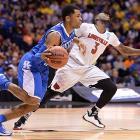 Andrew Harrison dribbles past Chris Jones as Kentucky eliminated the defending national champions.