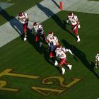 Members of the Washington State Cougars run across a memorial painted in the end zone for Tillman during their Pac-10 game against Arizona State in November 2004.