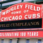 """All decked out for the celebration of its 100th Birthday, Wrigley's sign, crudely translated, means """"Abandon all hope ye who enter here."""""""