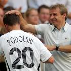 Lukas Podolski receives congratulations from Klinsmann during the 2006 World Cup Round of 16 match against Sweden in Munich.