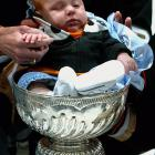 Goaltender Jean-Sebastien Giguere planted his infant son in the Stanley Cup after the Ducks thumped the Ottawa Senators 6-2 in Game 5 at Honda Center in Anaheim, Calif., becoming the first California-based NHL team to capture the chalice.