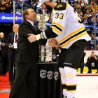 """The 6'-'9"""", 255-pound Bruins captain towered over the NHL's commissioner as he accepted the Stanley Cup after Boston defeated Vancouver in Game 7."""