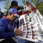Takuma Sato, of Japan, signs a poster for a fan during an autograph session before the drivers meeting for the Indianapolis 500.
