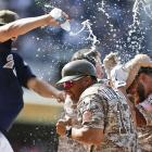 Yonder Alonso, right, is sprayed with water by teammates as they celebrate his game-winning RBI against the Arizona Diamondbacks in the bottom of the ninth inning on May 4.