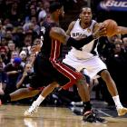 LeBron James makes a pass while being defended by Kawhi Leonard. The Spurs forward fouled out in the fourth quarter.