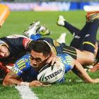 Ken Sio of the Parramatta Eels beats Johnathan Thurston of the North Queensland Cowboys for a try in the corner during a round 13 NRL match in Sydney, Australia.