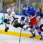 Chris Kreider (20) finishes a check on Kyle Clifford (13).