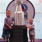 Here's a picture of my sons (Arno C. and Nikolaus, left to right) and the Cup while visiting the HHOF back in July of 2003. Both of my sons play hockey back home in Klagenfurt, Austria. (Home town of NY Rangers' Thomas Pock.) They are such big hockey fans that the day we arrived in Toronto, they insisted on going to the HHOF to see the Cup even though they were totally beat from the long travel from Austria (as you can probably tell by their expressions). -- Arno M. Groll