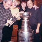 """This photo was taken at a 2002 Christmas party at a friend's house in Troy, Mich. His sister-in-law was employed by Marian Illitch and arranged to have the """"Blessed Cup"""" sent to the house as a surprise (OH YEAH!!!!).  In the picture (l-r): Mark Dembowski, Bobbie Dembowski, Rosie Jokinen, and Denny Jokinen (No relation to Olli or Jussi).  I actually was allowed to hold the cup Stevie Yzerman style over the head as it made its royal entrance. My wife's comment was """"This is really exciting for you isn't it?"""" My reply """"Better than sex ... right now."""" -- Mark Dembowski"""