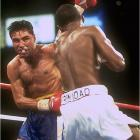 """Forget the Odd Couple jokes. Oscar and Felix was a match fight fans had been dreaming about. This showdown between two undefeated welterweight champions featured the straight-ahead power of Puerto Rican national hero Trinidad (whose record of 35-0-0 included 30 KOs) against the mobility and boxing skill of De La Hoya. For most of the bout, Oscar put on a dazzling display, circling, jabbing and completely neutralizing Trinidad's attack. But in the closing rounds, believing he """"had it won,"""" De La Hoya went on the defensive and coasted to the final bell. It cost him, as the judges gave Trinidad a majority decision."""