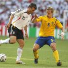 Bernd Schneider (left) holds off Sweden's Erik Edman in Germany's 2-0 victory.