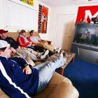 After a tough day on the ice, the guys kick their feet up on a bottle cap-covered coffee table and relax in front of their 65-inch flatscreen TV.