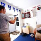 Nate Davis shoots some darts while Brad Robbins looks on.