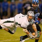 A lacrosse player from Duke is blocked by a flying defenseman.