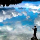 Jason Romero fishes in Bremerton, Wash., as the clouds are reflected in the calm, serene water.