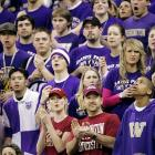 Two brave Washington State fans stand and cheer in front of the Washington student section during the Cougars 65-61 victory on Wednesday.