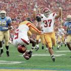 """I like to say that Reggie Bush is flipping out in this photo. Two plays before Bush scored on this long run against UCLA, I was at the line of scrimmage, and I thought, What if Reggie breaks a long run? So I bolted to the end zone, and lo and behold, he broke off this touchdown run. And I was fortunate that his teammate was raising his arms, signaling touchdown. As fellow photographer Walter Iooss says, """"Sometimes luck favors the prepared.""""<br><br>Shot with: Canon EOS-1D Mark II N, EF 70-200mm f/2.8L IS USM lens"""
