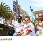 Washington Nationals first baseman Dmitri Young waves to fans while taking a ride with his family down the red carpet on their way to San Francisco's AT&T Park for the game.