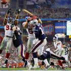 Kawika Mitchell (55) and Justin Tuck (91) pressure Tom Brady for an incomplete pass from the New England 5-yard line in the third quarter.