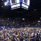 Kansas fans celebrate on the floor of Allen Fieldhouse after the Jayhawks won the NCAA basketball championship.